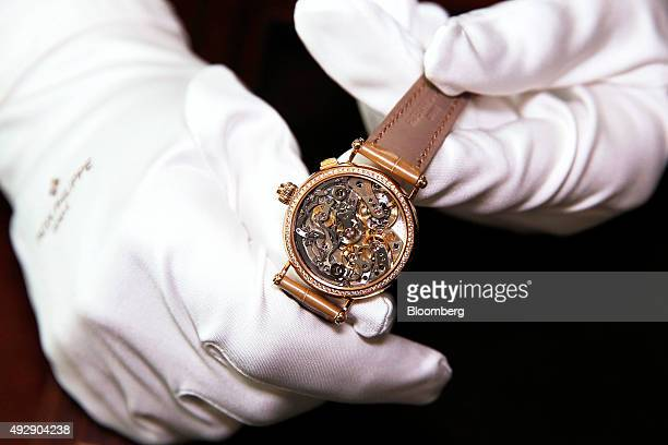 A watchmaker displays the workings of a Patek Philippe SA ladies Grand Complications 7059 luxury wristwatch at the Patek Philippe SA headquarters and...