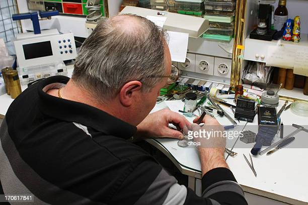 Watchmaker in his office...repairing wrist watch,chaos on the table