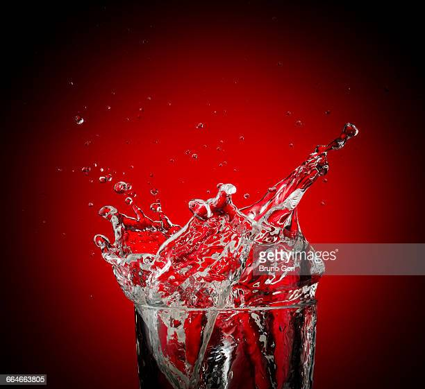 Water and droplets splashing against red background