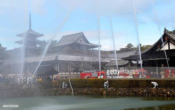Water are discharged during the annual fire drill at the World Heritage Horyuji Temple on January 26 2014 in Ikaruga Nara Japan