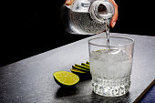 Water being poured into a glass next to sliced lime