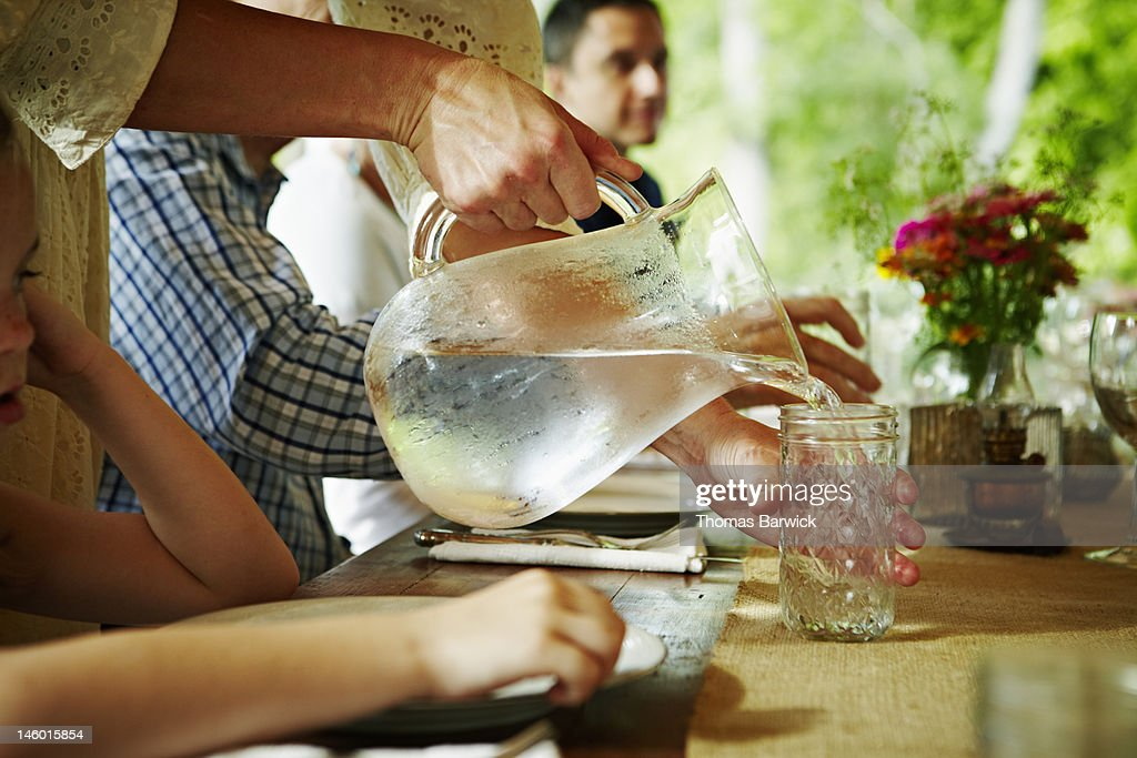 Water being poured into glass at table on porch