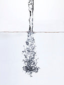 Water being poured into water, surface view, studio shot