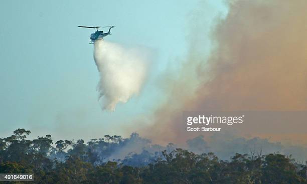 A water bombing helicopter dumps water on a bushfire in Lancefield Victoria on October 7 2015 near Melbourne Australia Victorian fire crews have been...