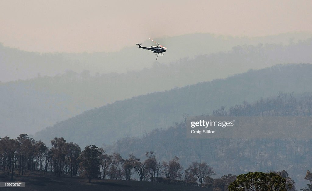 A water bombing helicopter fights fires that threaten a house near the town of Glenmaggie on January 19, 2013 in Australia. Bushfires in Victoria have claimed one life and destroyed several houses. Record heat continues to create extreme fire conditions throughout Australia.