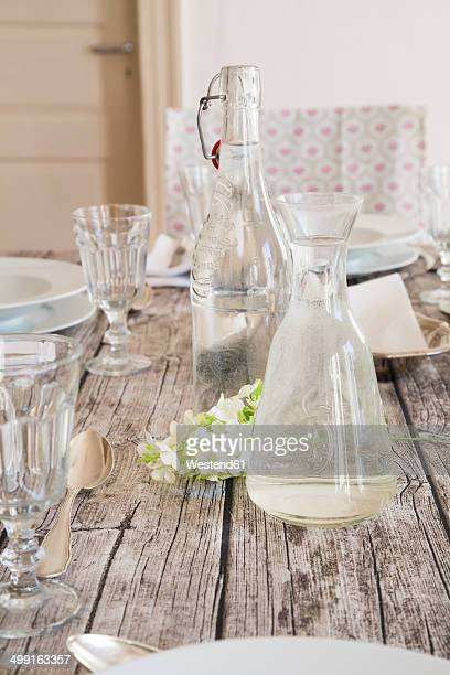 Water bottle, carafe, glasses and white blossom on festive laid table