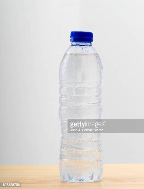 Water bottle of transparent plastic fries, with water drops esmerilado in his surface on a white background