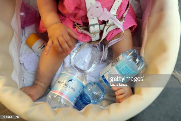 Water bottles are seen in a baby stroller while tourists walk around the city as Florence experiences increasingly high temperature on August 3 2017...