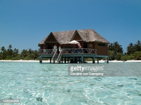 Water bungalow with couple on terrace : Stock Photo