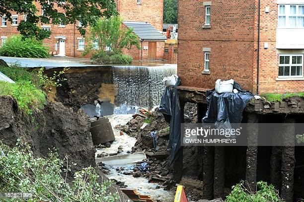Water continues to cascade over the end of where a landslip caused by flooding has cut across a road outside a block of flats where the foundations...