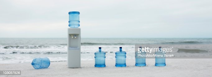 Water cooler and water jugs lined up on beach