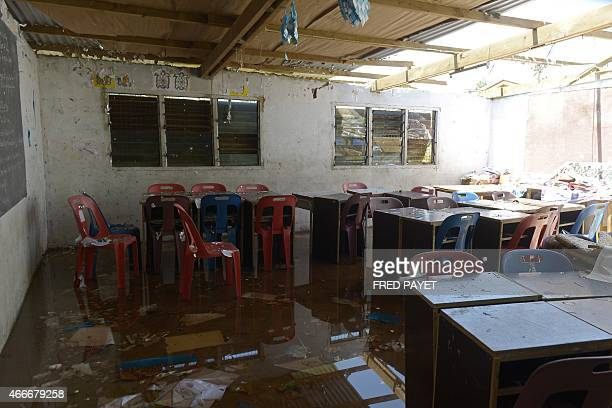 Water covers the ground at a damaged school in Port Vila on March 18 2015 after Severe Tropical Cyclone Pam hit the Pacific nation of Vanuatu Aid was...