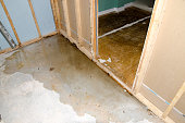 View of a concrete basement floor full of water caused by sewer backflow due to clogged sanitary drain