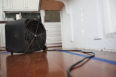 Industrial fan drying out residential kitchen island from water damage caused by leak.