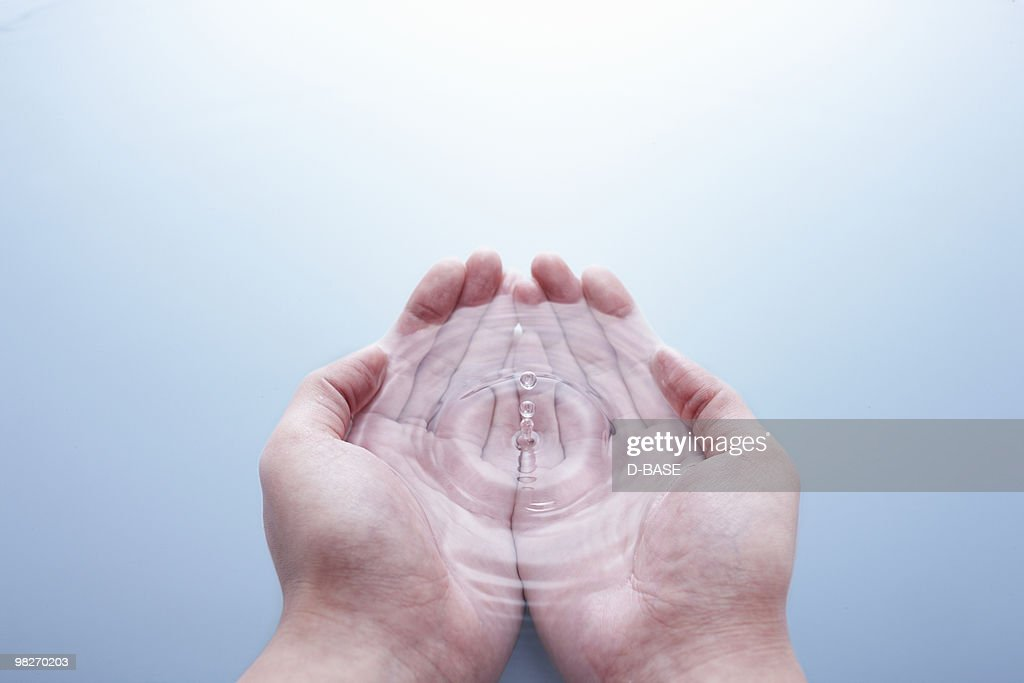 Water dripping on hand : Stock Photo