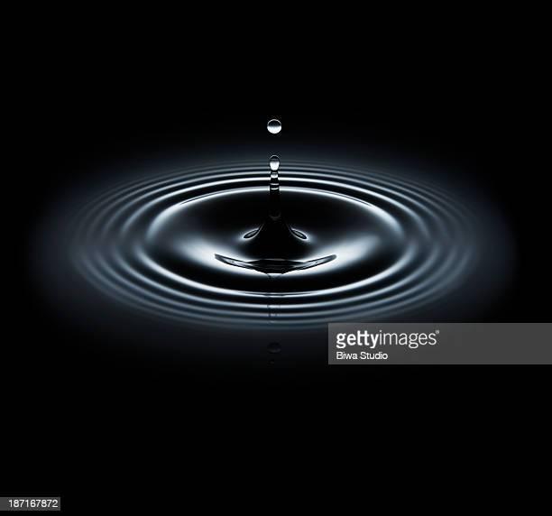Water drop making ripple on black background