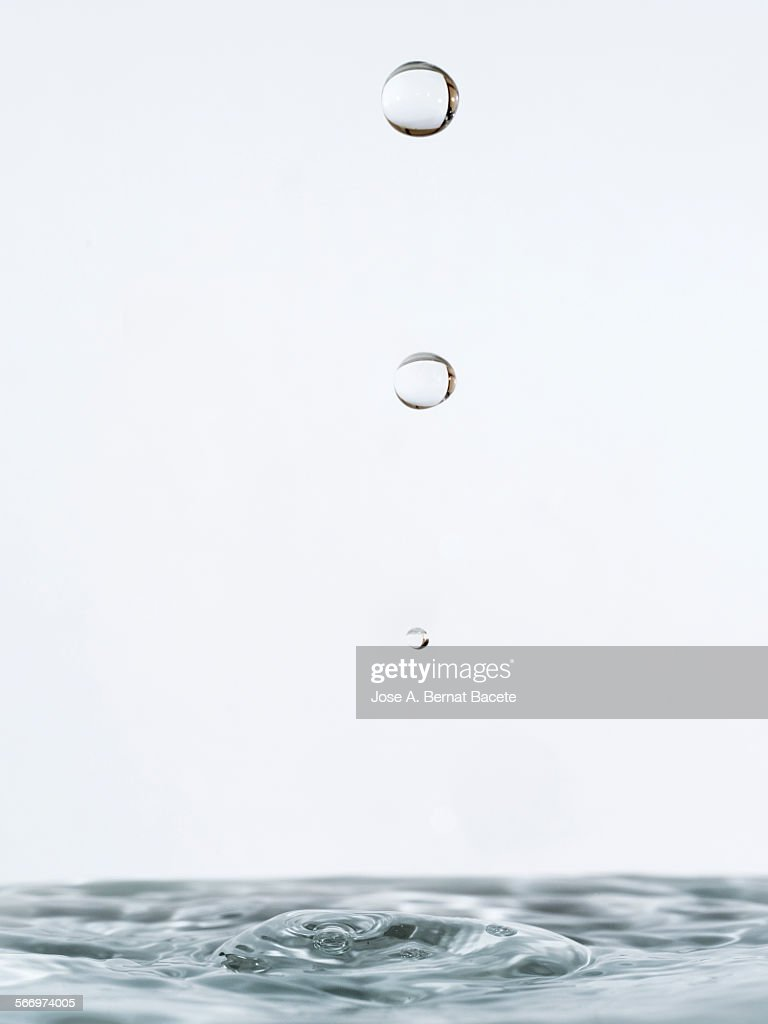 Water drop striking on stagnant water : Stock Photo
