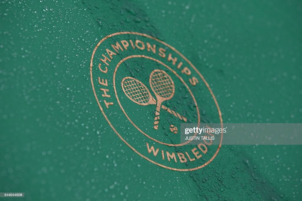 Water droplets cascade down an umbrella as rain stops play on the fifth day of the 2016 Wimbledon Championships at The All England Lawn Tennis Club in Wimbledon, southwest London, on July 1, 2016. / AFP / JUSTIN