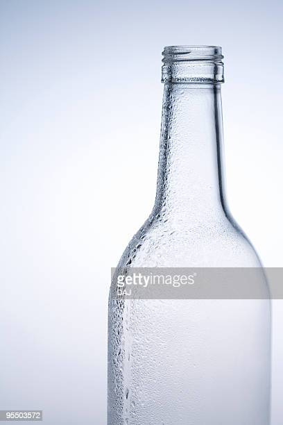 Water drops on a glass bottle, close up, white background
