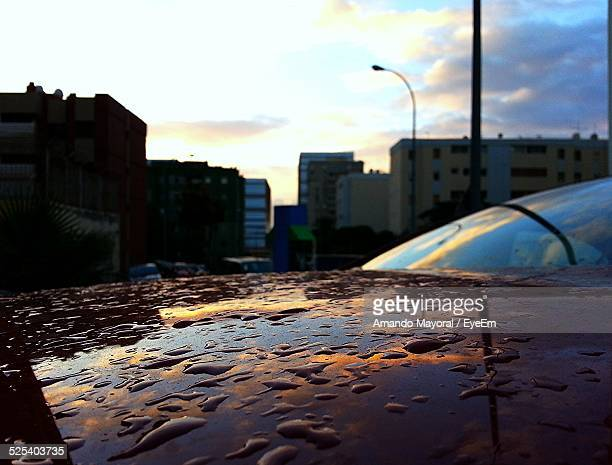 Water Drops On Car Hood With Buildings In Background