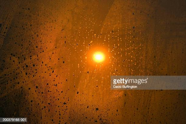 Water drops on window, sun in background, sunrise, view through window
