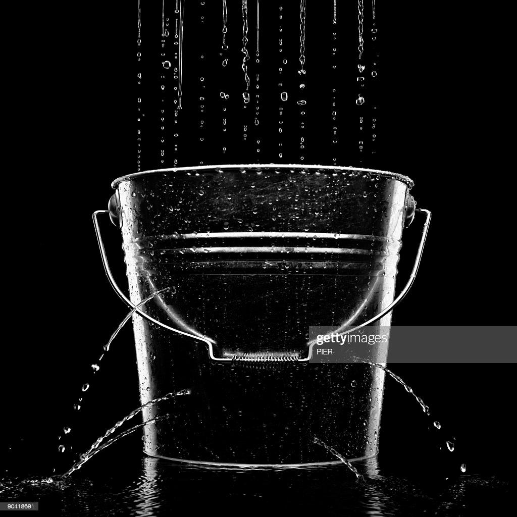 Water falling into a leaking metal bucket
