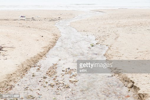 water flowing from the beach into the sea : Stockfoto