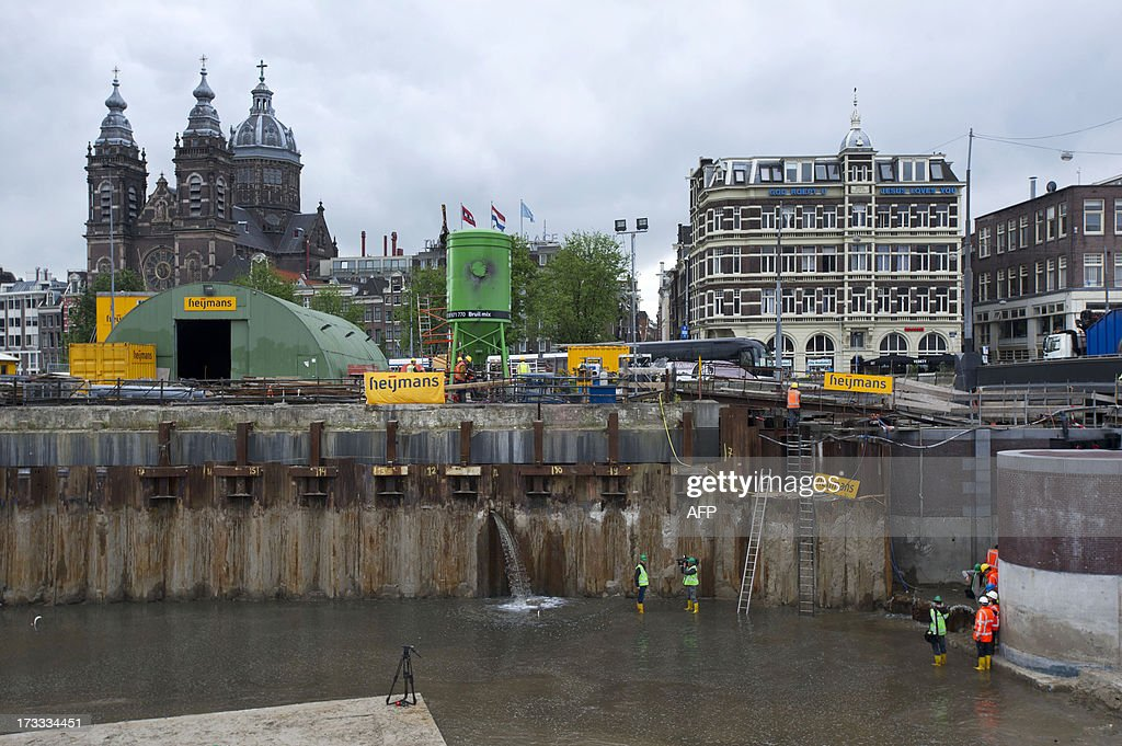 Water flows on July 12, 2013 through a hole in the dam during the construction of the North-South metro line in Amsterdam, The Netherlands. Water was cut in the area around Amsterdam's Central Station due to the construction on the North-South metro line. AFP PHOTO / ANP / EVERT ELZINGA -- The Netherlands out --