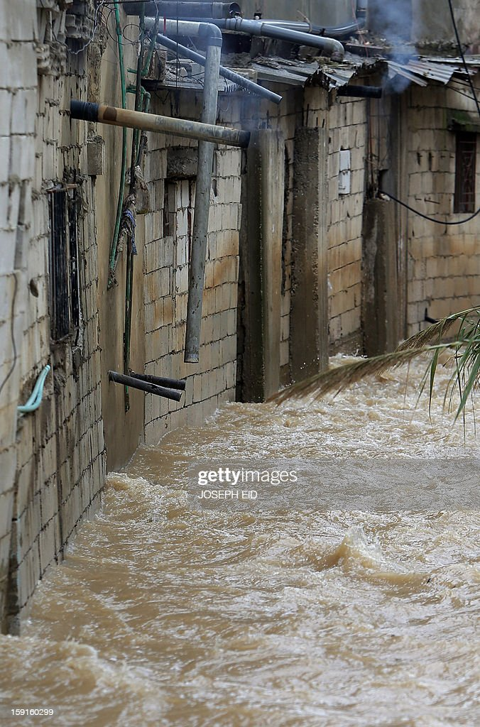 Water flows past flooded houses in Beirut's southern suburb of Hayy al-Sellum on January 9, 2013 as heavy rains and high speed winds hit Lebanon. A met office official at Beirut airport said the storm would continue and that lower temperatures would result in snowfall in the mountains as low as 300 metres. AFP PHOTO /JOSEPH EID