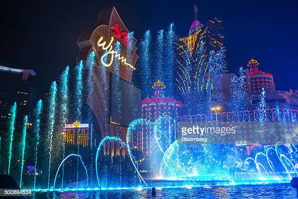 Water from a fountain sprays into the air in front of signage for the Wynn Macau casino resort operated by Wynn Resorts Ltd left as the Casino Grand...