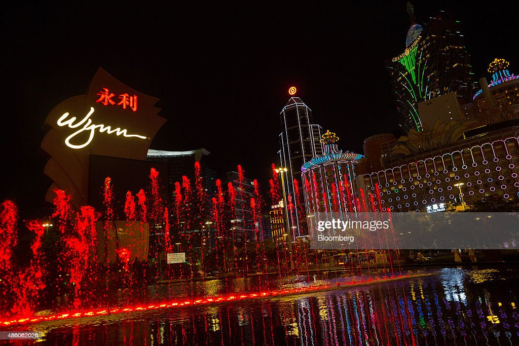 Water from a fountain sprays into the air in front of the signage for Wynn Macau casino resort operated by Wynn Resorts Ltd left the Bank of China...