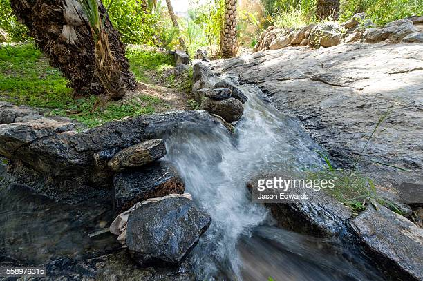 Water from a mountain spring running down a falaj in an ancient village.