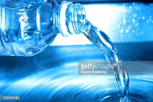 Water from a water bottle is being poured out into a pool of water : Stock Photo