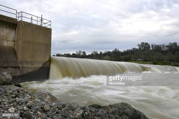Water from the Feather River rushes over a berm at the Feather River Fish Hatchery in Oroville California US on Wednesday Feb 15 2017 Crews worked...