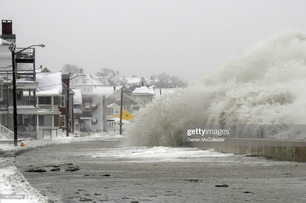 Water from the ocean crashes over the sea wall along Winthrop Shore Drive on February 9, 2013 in Winthrop, Massachusetts. The powerful storm has knocked out power to 650,000 and dumped more than two feet of snow in parts of New England.