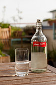 Water glass and bottle on table in garden
