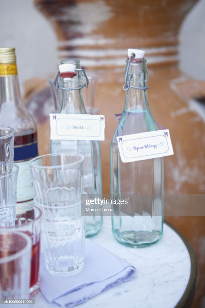 Water in bottles with empty glasses, close-up : Stock Photo