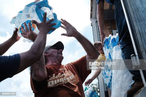 Water is passed out to residents in a rural migrantworker town waiting for emergency donations following Hurricane Irma on September 14 2017 in...
