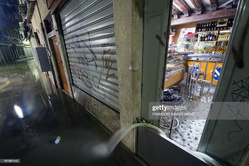Water is pumped from a shop during an acqua-alta (high-water) late on February 11, 2013 in Venice. The 'acqua alta', a convergence of high tides and a strong sirocco, reached 143 centimetres around midnight.
