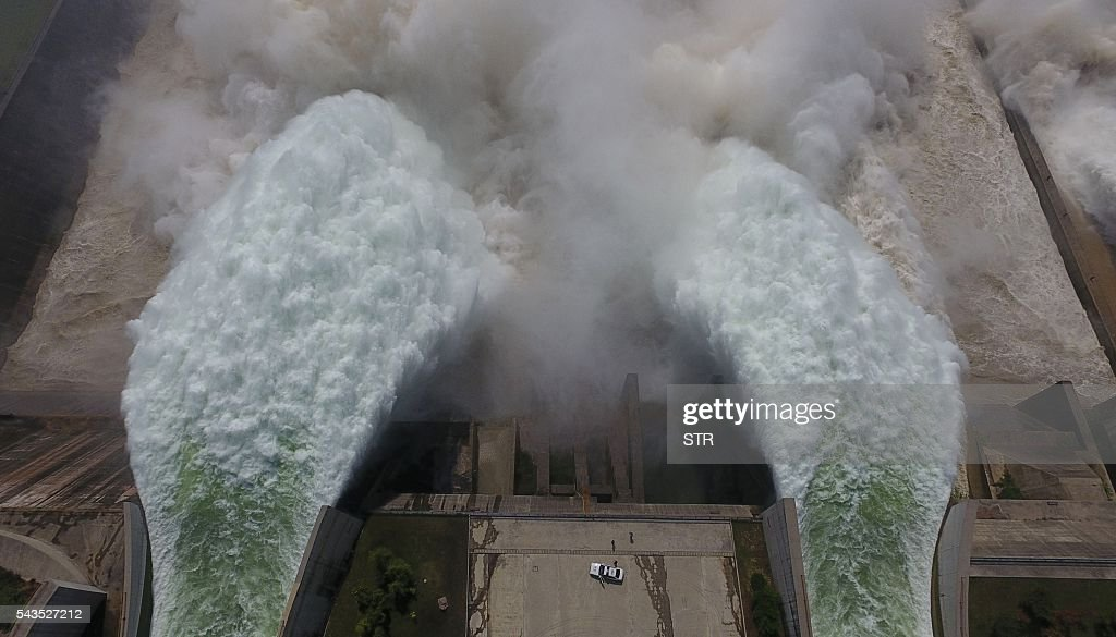 Water is released from the floodgates of the Xiaolangdi dam on the Yellow River, as policemen (bottom) look on near Luoyang, in China's Henan province on June 29, 2016. The floodgates are opened every year in an operation to flush millions of tonnes of silt from the river bed. / AFP / STR / China OUT