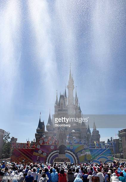 Water is sprayed as the Walt Disney Co character Donald Duck center performs in front of the Cinderella Castle during an event named 'Disney Natsu...