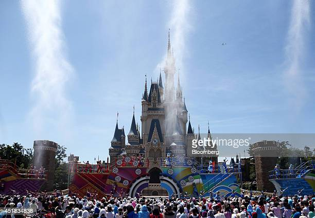 Water is sprayed as the Walt Disney Co characters Mickey Mouse center left Donald Duck center right perform in front of the Cinderella Castle during...