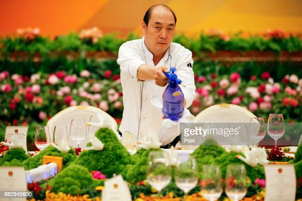 Water is sprayed on the table prepared for heads of states before the welcoming banquet at the Great Hall of the People during the first day of the...