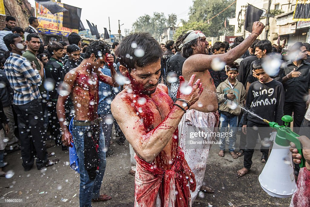 Water is sprayed onto Shiite Muslim men as they beat their chests, holding razor blades, as part of a self-flagellation ritual during a religious procession marking Ashura on November 25, 2012 in New Delhi, India. The religious festival of Ashura, which involves a ten-day mourning period starting with the first day of Muharram on the Islamic calendar, commemorates and mourns the seventh-century martyrdom of Prophet Muhammad's grandson Imam Hussein in the battle of Karbala.