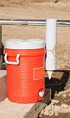 'water jug, orange plastic'