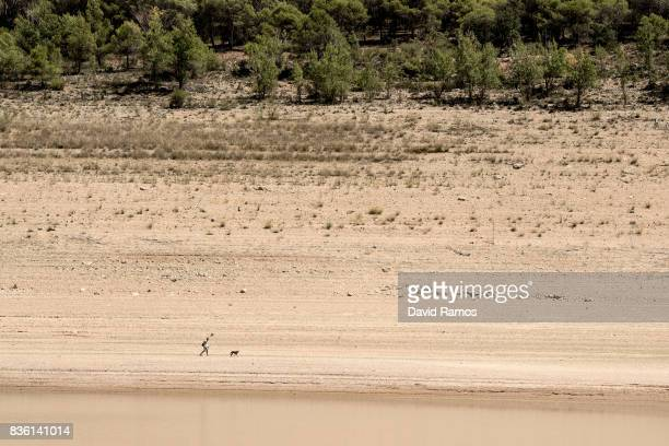 Water lines are visible as a man walks his dog along the bank of Entrepenas reservoir second largest water reservoir feeding the Segura River and...