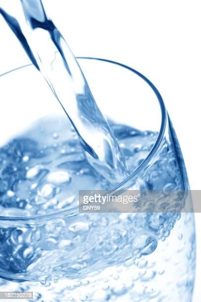 peing Wasser gegossen in ein Glas auf weißem Hintergrund