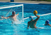 Side view of water polo players having goal action