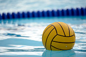 A yellow blue water polo balls rests in a water.