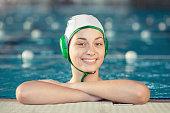 Girl water polo player on pool edge.